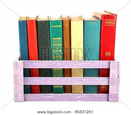 Books in wooden box isolated on white