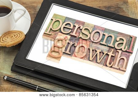 personal growth typography - text in letterpress wood type on a digital tablet with a cup of coffee