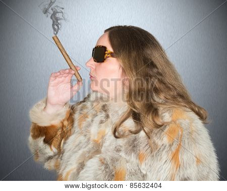 Woman with fur coat and sunglasses smokes a cigar