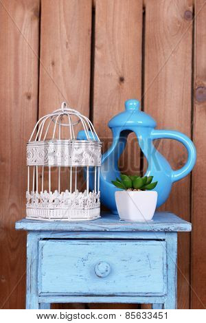 Interior design with decorative pot, cage and plant on tabletop on wooden planks background