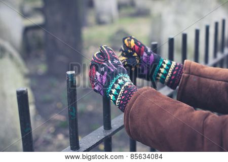 Gloved Hands Holding Fence At Graveyard