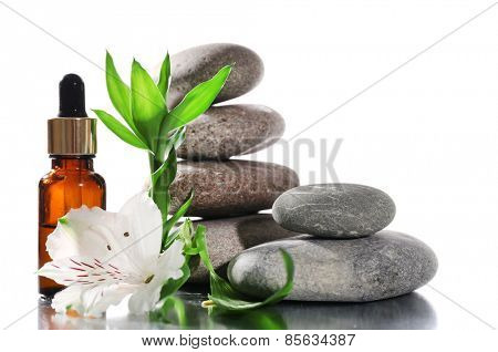 Spa stones with aromatic oils and flower isolated on white