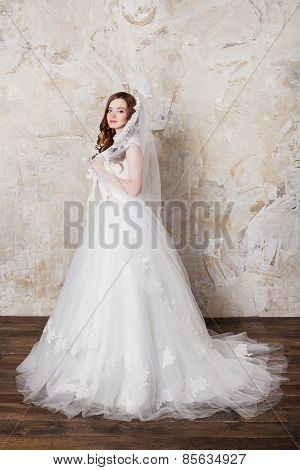 Slim beautiful woman with long hair wearing luxurious wedding dress