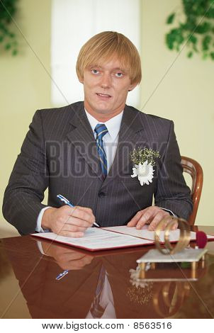 Groom Puts Signature On Registration Document