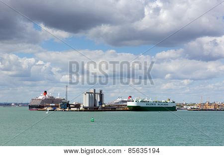 View of Southampton Docks with big cruise ship and cargo vessel on calm summer day with fine weather