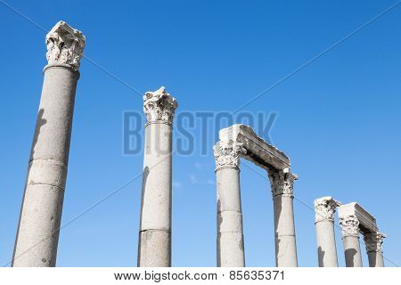 Ancient Columns In A Row On Blue Sky Background