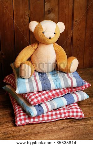 Bear toy on pillows on wooden background