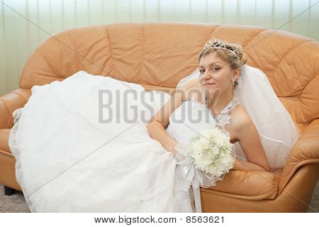 Bride Comfortably Lies On Big Leather Sofa
