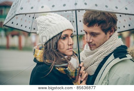 Young Couple Looking Under Umbrella In A Rainy Day