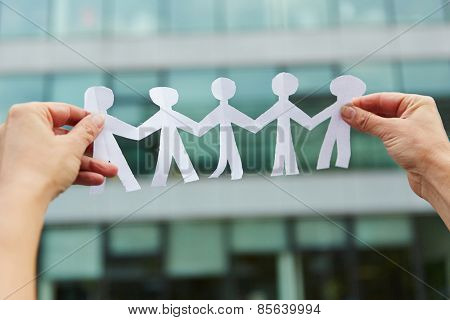 Family with people made of paper held in hands