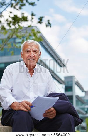 Happy old lawyer with contract sitting outside in summer