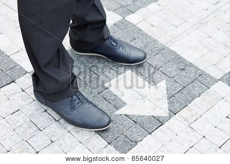 Arrow in front of shoes showing direction for a business man