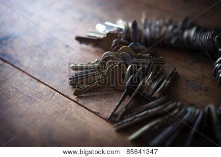 Many old keys placed on a well used old wooden desk with incoming light. Security and encryption, concept image.