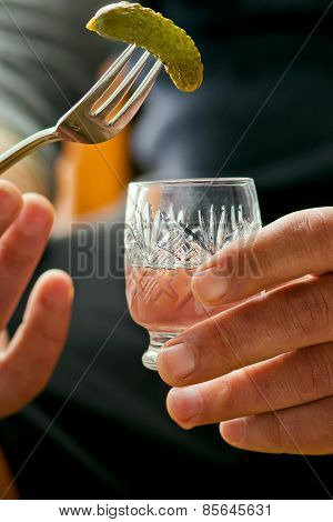 glass of vodka and pickled cucumber on a fork in male hands.