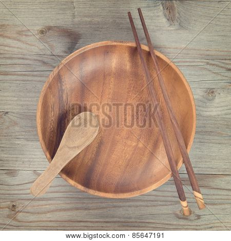 Overhead view of empty plate and sushi chopsticks on old wooden table. View of dining setting in vintage mood. Square composition.