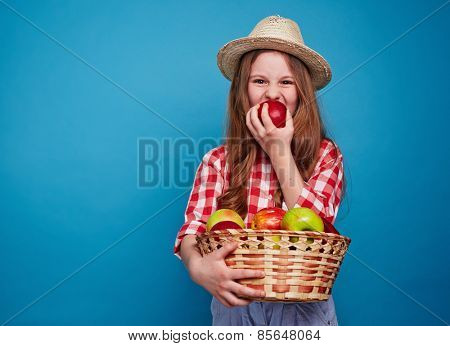 Cute girl biting red apple and holding a basket with fruits