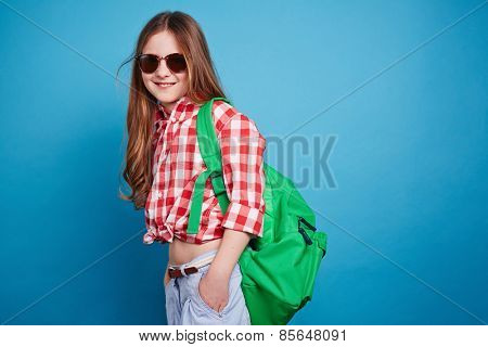 Little girl with knapsack looking at the camera