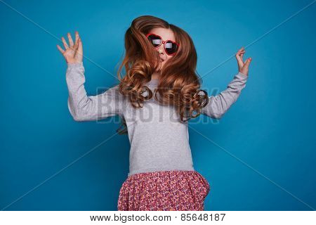 Girl in red heart-shaped glasses jumping