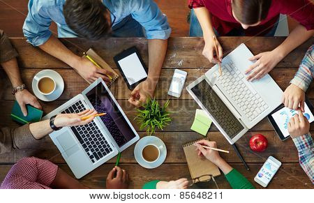 High angle view of people meeting at table and working with laptops and touchpads
