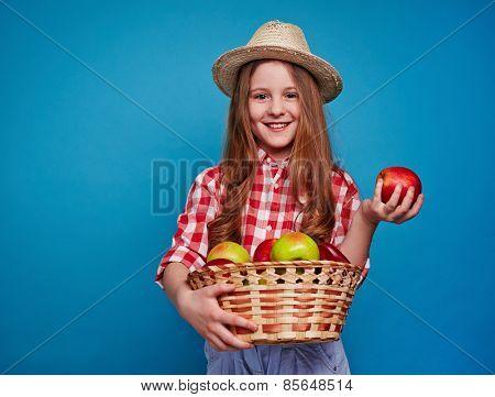 Smiling girl keeping fruit basket