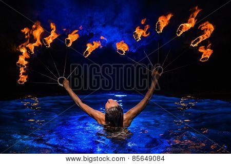 Firedancer woman with fire in water