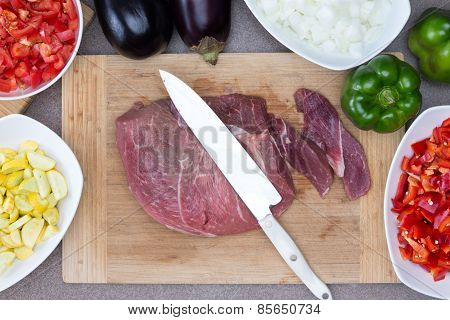 Meat On Chopping Board With Ingredients On Sides