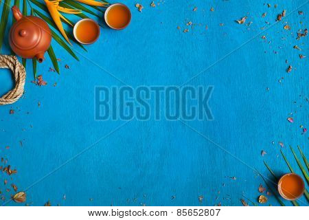 Teapot, Teacups, Green Leaves And Yellow Flower On Blue Wooden Background.
