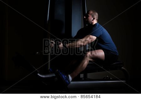 Young man at the gym on rowing machine in full force.Young man working back muscles