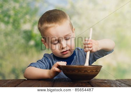 Cute Little Boy Eats Outdoors