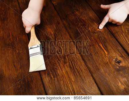 Baby Hand Applying Protective Varnish On A Wooden Table