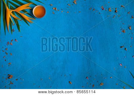 Teacup With Shuck, Green Leaves And Yellow Flower On Blue Wooden Background. Top View.