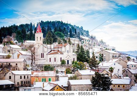 Small Mediterranean Town On The Slopes Of Hill With A Church On Top, Covered In Snow