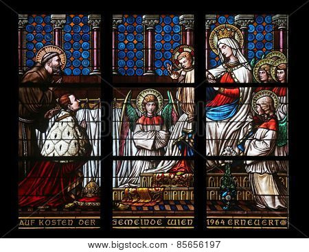 VIENNA, AUSTRIA - OCTOBER 10: Virgin Mary with baby Jesus, angels and Saints, Stained glass in Votiv Kirche (The Votive Church). It is a neo-Gothic church in Vienna, Austria on October 10, 2014