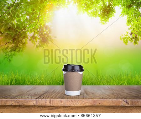 Paper cup of coffee on Wood table in nature