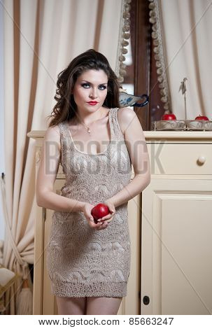 Beautiful sexy woman in nude colored lace dress in vintage scenery holding a red apple
