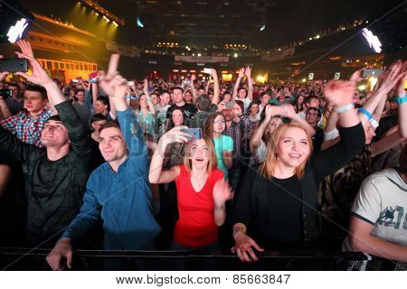 MOSCOW - APR 05, 2014: A crowd of happy young people with their hands raised at the disco in Stadium Live