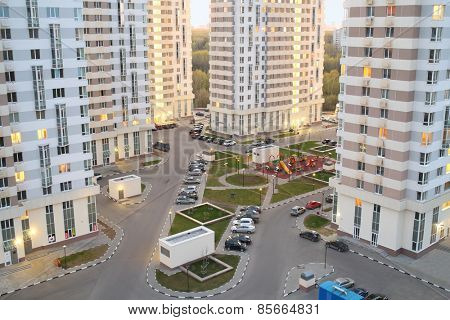MOSCOW, RUSSIA - APR 23, 2014: Courtyard with tall buildings, parking and playgrounds in modern residential complex Elk Island in the evening, top view