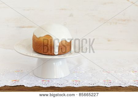 Kulich, Traditional Russian Easter Cake With Royal Icing On White Pedestal And White Cloth