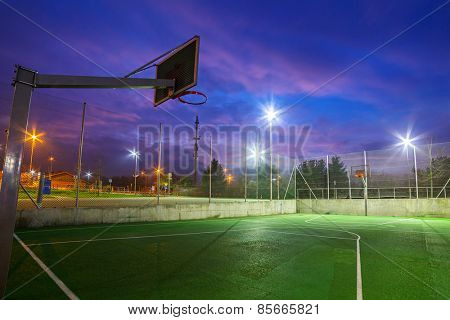 Basketball court illuminated at dusk