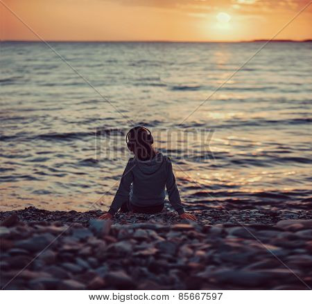 Young Woman In Headphones Sitting On Beach At Sunset