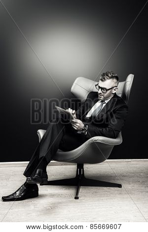 Imposing mature man in elegant suit sitting on a leather chair in a modern luxurious interior and working on a laptop. Fashion. Business. Black-and-white portrait.