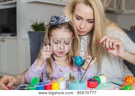 Mother And Daughter Painting Easter Eggs In Home