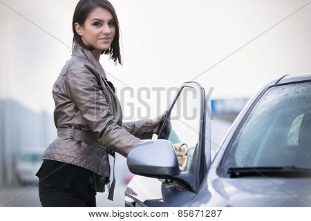 Young woman, driver, dry wiping her car with microfiber cloth after washing it, cleaning automobile
