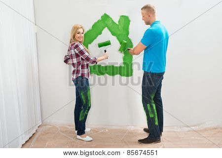 Couple Painting Green Home On Wall