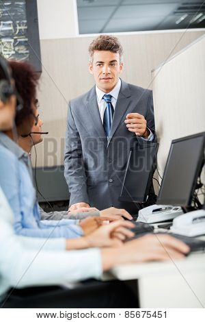 Confident manager discussing with customer service representatives in office