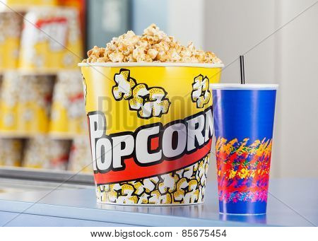Popcorn bucket and cold drink on cinema concession stand