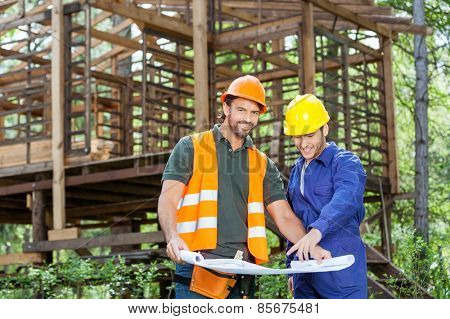 Portrait of smiling architect with colleague explaining blueprint outside incomplete wooden cabin at construction site