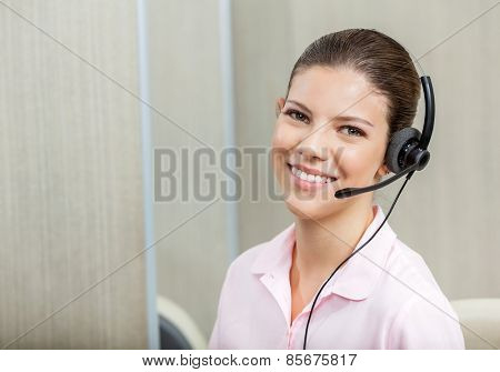 Portrait of smiling female customer service executive wearing headset in call center