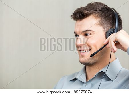 Closeup of happy male call center employee using headset while looking away at office