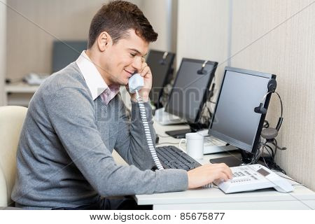 Young male call center employee using landline phone in office